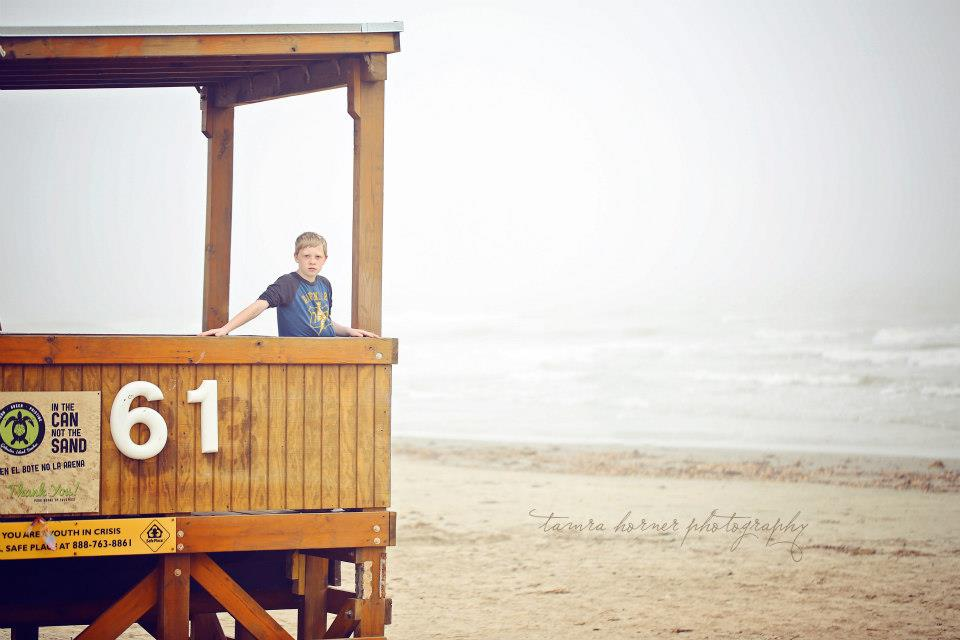 boy in a lifegard tower galveston tx photographer